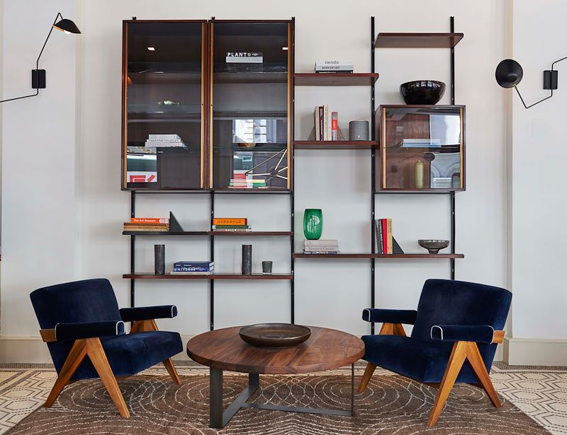 Picture of two wooden chairs with navy cushions, facing each other at an angle, with a wooden coffee table in between - in the lobby of Walker Hotel Tribeca. A open book shelf can be seen in the background, behind chairs.