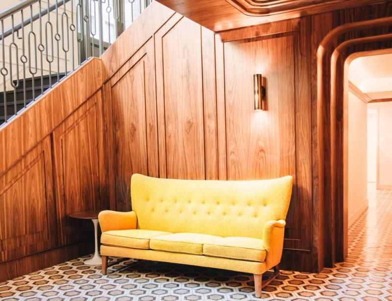 Yellow decorative couch next to wooden stairway in the lobby of Walker Hotel Tribeca